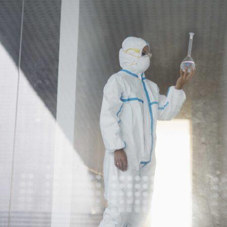 Biochemist in clean suit examining beaker with liquid in laborat
